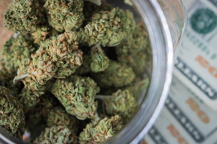 jar of cannabis flower and twenty dollar bills
