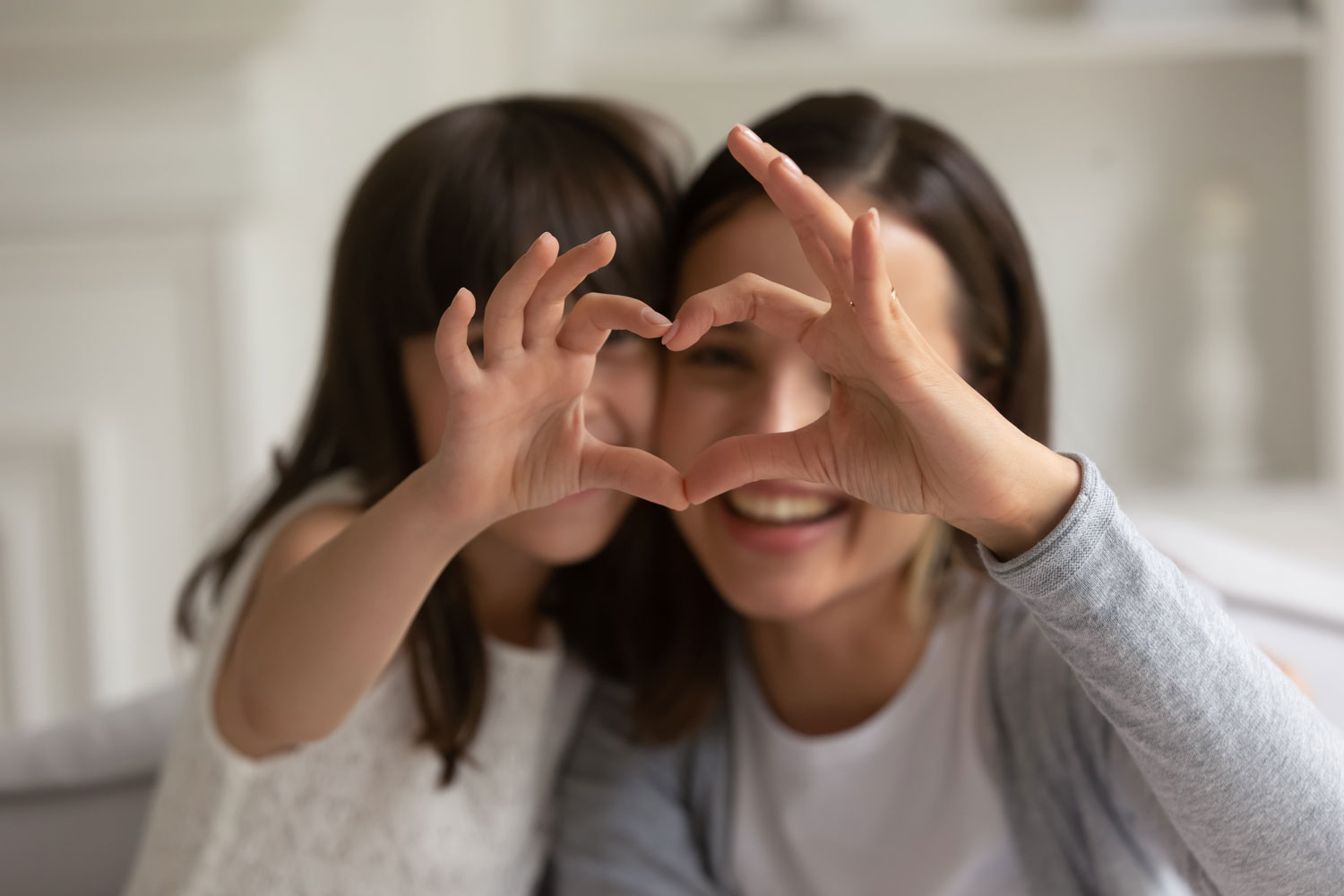happy young mother with little daughter making focused heart sign